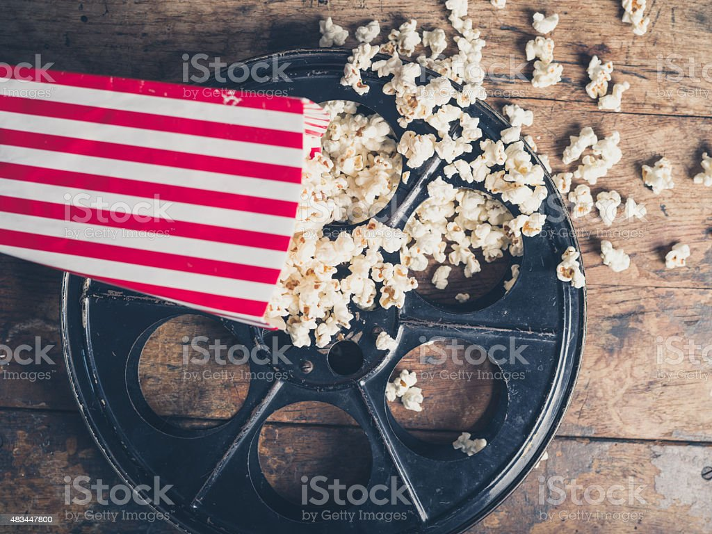 Film reel and popcorn stock photo