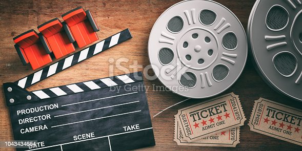istock Film reels with retro cinema tickets, movie clapper and red theater seats on wooden background. 3d illustration. 1043434654