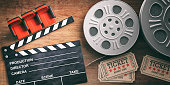 Cinematography concept. Film reels with retro cinema tickets, movie clapper and red theater seats on wooden background. 3d illustration.