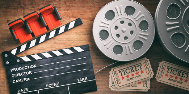 Film reels with retro cinema tickets, movie clapper and red theater seats on wooden background. 3d illustration. stock photo
