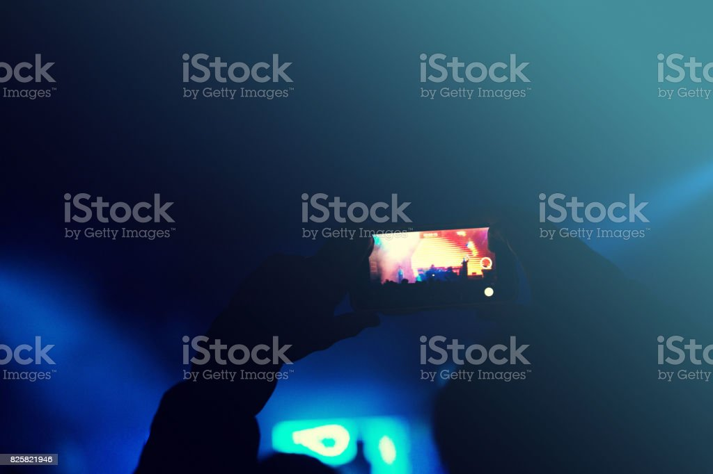 filming at concert stock photo