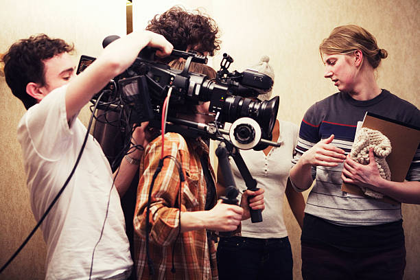 Filming crew of three people shooting two girls talking stock photo