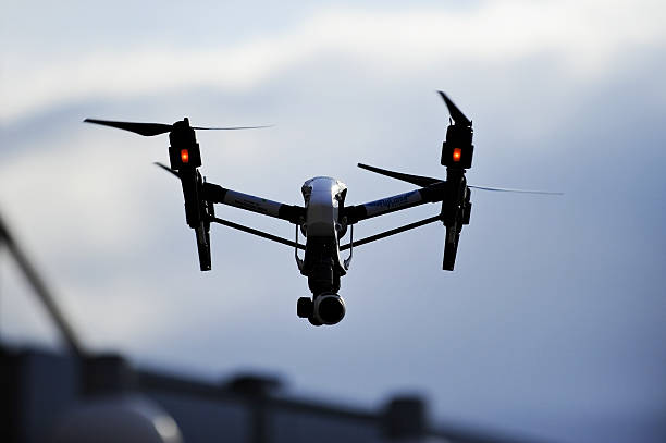 filming drone silhouette - big brother orwellian concept stock pictures, royalty-free photos & images