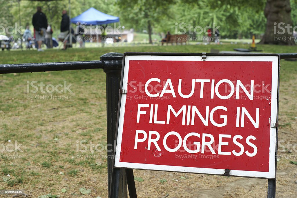 Filming in progress sign by the park fence