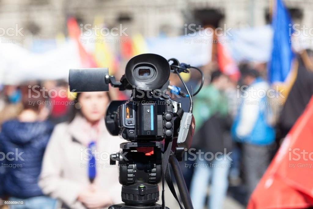 Filming street protest using a video camera. Media covering of a demonstration. royalty-free stock photo