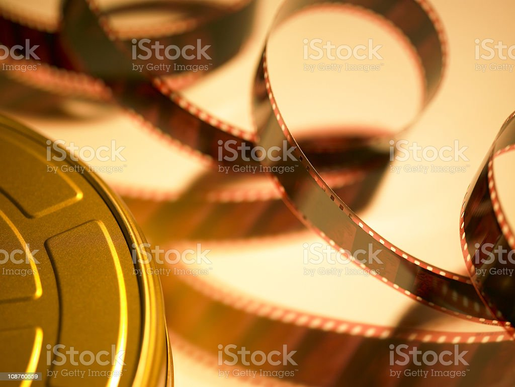 Filmstrip coming out of golden movie reel royalty-free stock photo