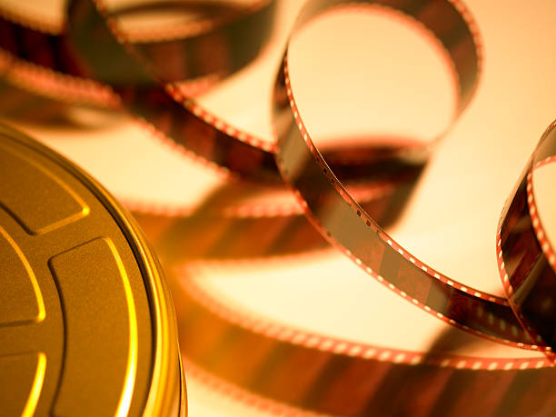 Filmstrip coming out of golden movie reel stock photo