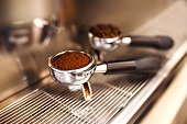 Filter holder with ground coffee and roasted coffee beans. Coffee machine preparing fresh coffee and pouring into cups at restaurant, bar or pub. Preparation service concept.