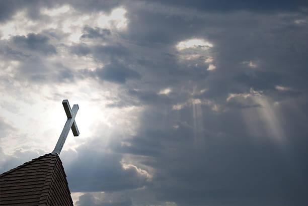 gefilterte sonnenlicht mit weißem kreuz und kirchturmspitze - kirchturmspitze stock-fotos und bilder