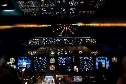 Final approach at night - landing plane flight deck view
