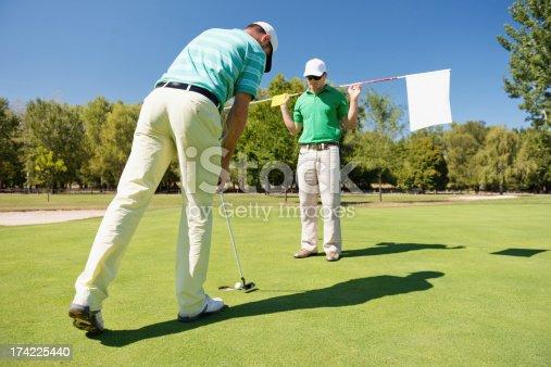 Golfer making final putt, caddy holding a flag
