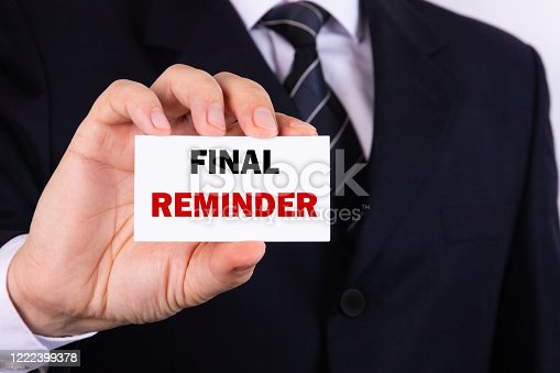 istock Final Reminder Businessman holding a card with a message text written on it. 1222399378