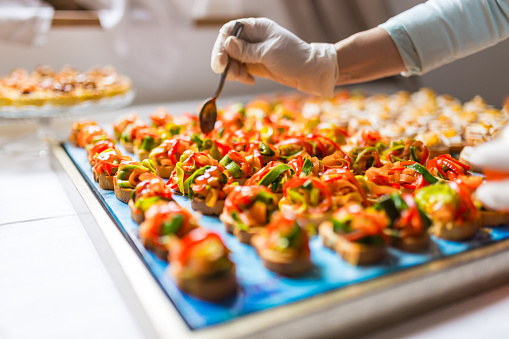 Chef is using gloves for adding the final dressing on delicious canapes
