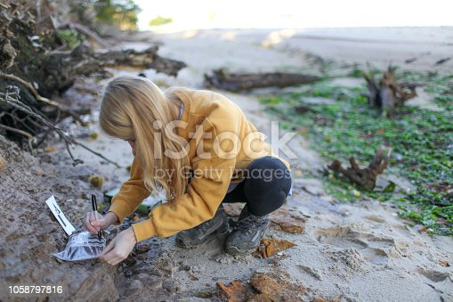 Final year female Geology student taking coastal rock samples and marking up sample bags in the South of England as part of her final year Geology dissertation on sea level changes in the UK