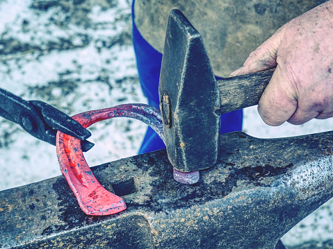 istock Finalize horseshoe, hitting hot metal with hammer 1217133656