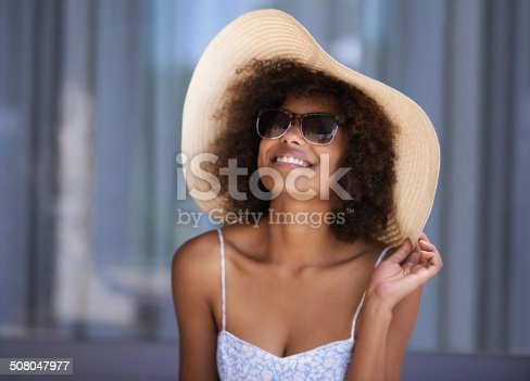 Shot of an attractive young woman wearing a sun hat relaxing outside