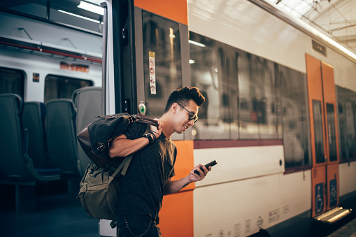 Handsome young chinese hipster waiting for a train at the train station.