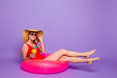 Finally vacation! Full-size portrait of young girl in a hat and glasses holds cocktail in her hand and lies on multi-colored inflatable circle isolated on violet background with copy space for text