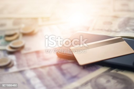 istock Finance and online shopping concept. Golden color credit card and mobile smart phone on banknotes and coins. 927888460