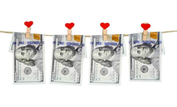 Finanzkonzept-Dollar-Banknoten, die an dem Seil hängen, das mit Liebeskleidungsstiften befestigt ist – Foto