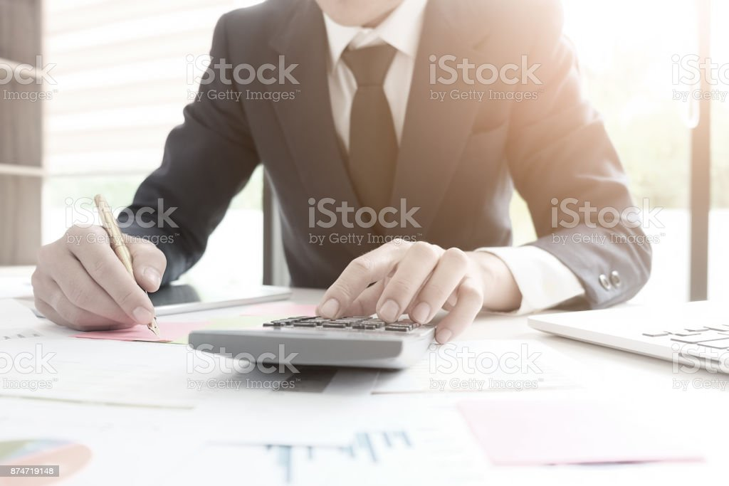 Finance concept,finance control audit man calculate business financial data on calculator. stock photo