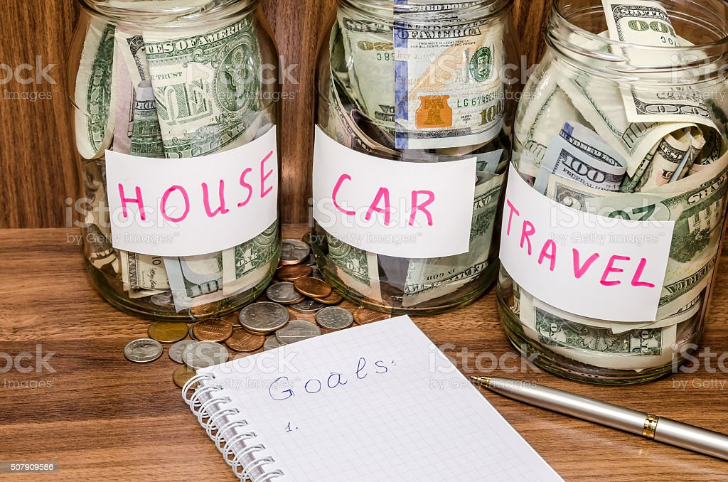finance idea - new years resolutions with dollar coins finance idea - new years resolutions with dollar in glass jar, coins on wooden table Aspirations Stock Photo