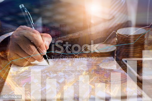 istock Finance, profit, capital banking and investment concept, Double exporsure stacked of coins and night city with graph 1027150010