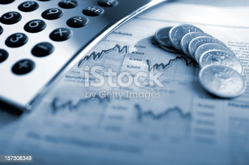 A close up, blue tinted conceptual image of silver calculator and British ten pence coins on top of a generic financial newspaper page showing stock market graphs. The image illustrates the concepts of: finance, money, economy, stocks and investment. Shot with a shallow depth of field.