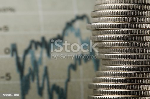 Coin stacking and newspaper stock market chart