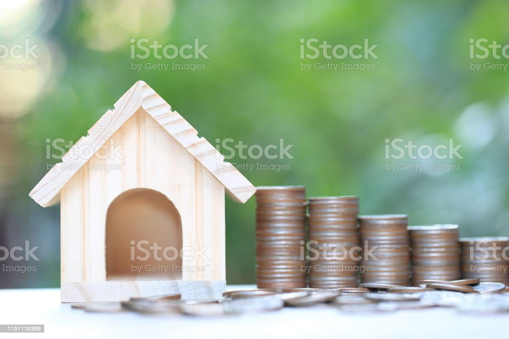 Finance, Stack of coins money and Model house on natural green...