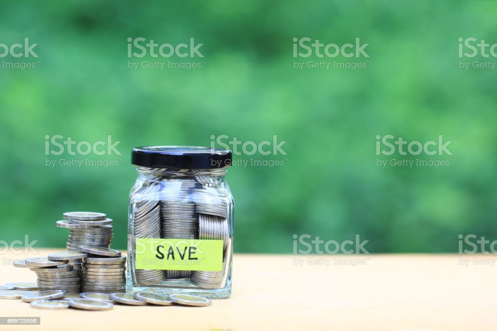 Finance, Stack of coins money in the glass bottle on natural green...