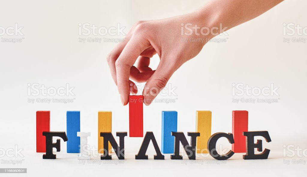 Red, blue and yellow wooden blocks of same height standing over white...