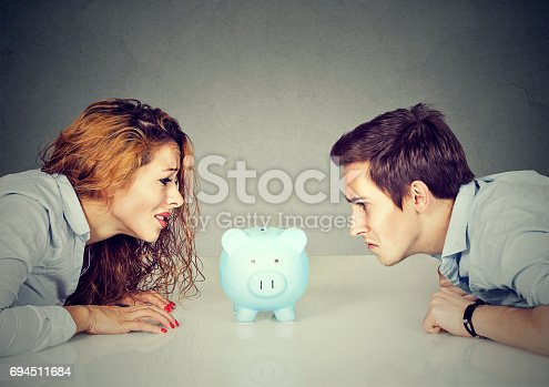 istock Finances in divorce concept. Wife and husband can not make settlement holding piggy bank sitting at table looking at each other with hatred 694511684
