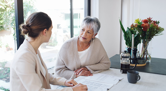 Shot of a senior woman meeting with a consultant to discuss paperwork at home