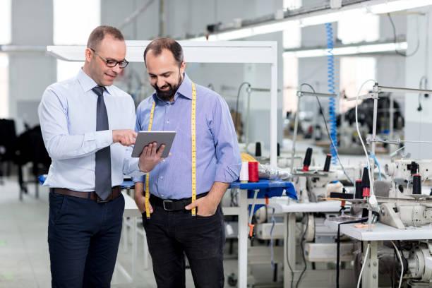 Finanzberater und Geschäftsmann mit Tablette in der Fabrik. – Foto