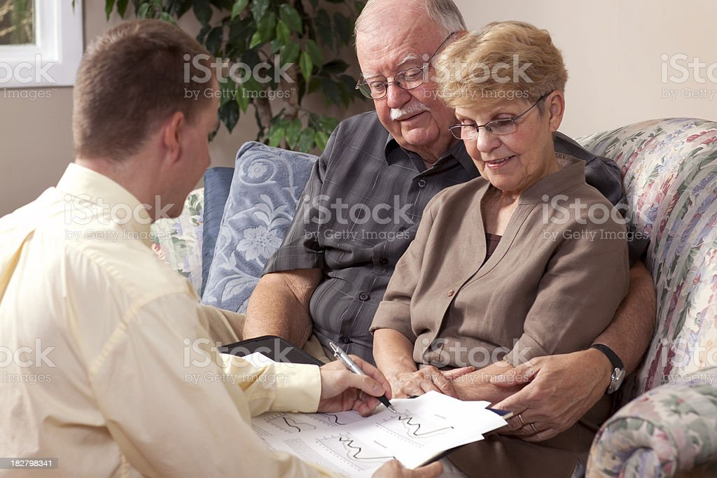 Financial advisor and seniors reviewing investment royalty-free stock photo