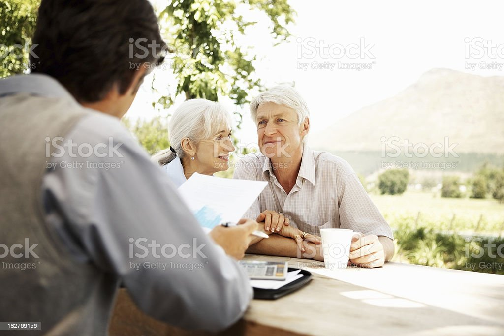 Financial advisor - Banking agent sitting with senior client royalty-free stock photo