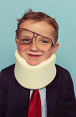 A young boy dressed up in business suit smiles after being beat up by the unpredictable economy. He is wearing a neck brace and has a black eye but is determined to conquer adversity.