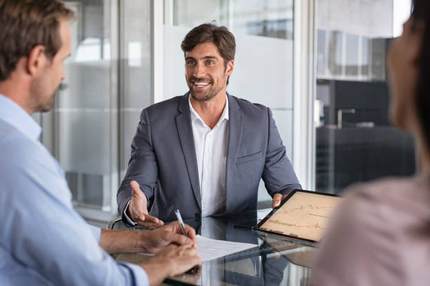 Financial advisor consulting Confident financial agent showing growth graph to couple. Mid couple meeting financial advisor for investment. Business people discussing the charts and graphs showing the results of their successful teamwork. insurance stock pictures, royalty-free photos & images