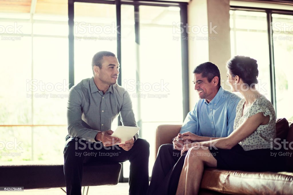 Financial advisor discussing with happy couple stock photo