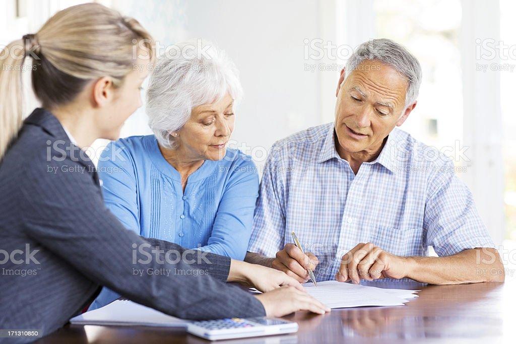 Financial Advisor Explaining Investment Plans To Senior Couple. royalty-free stock photo