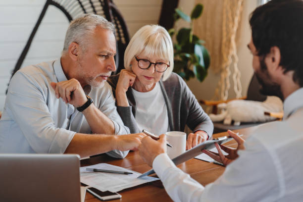Financial advisor explaining paperwork to elderly retired couple front of desk Financial advisor explaining paperwork to elderly retired couple front of desk plan document stock pictures, royalty-free photos & images