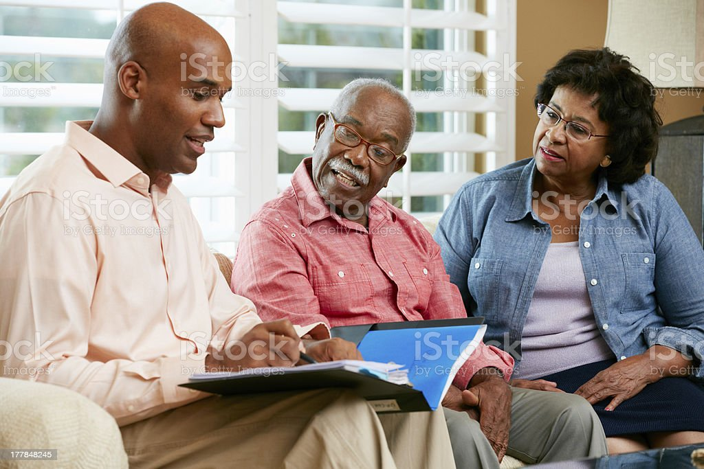Financial advisor going over some notes with senior couple stock photo