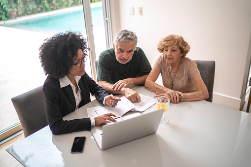 istock Financial advisor helping a senior couple at home 1146740420