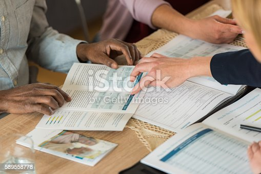 Financial advisor pointing brochure and explaining document to his customer.