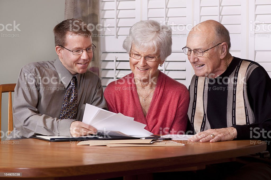 Financial advisor presenting documents to an elderly couple stock photo