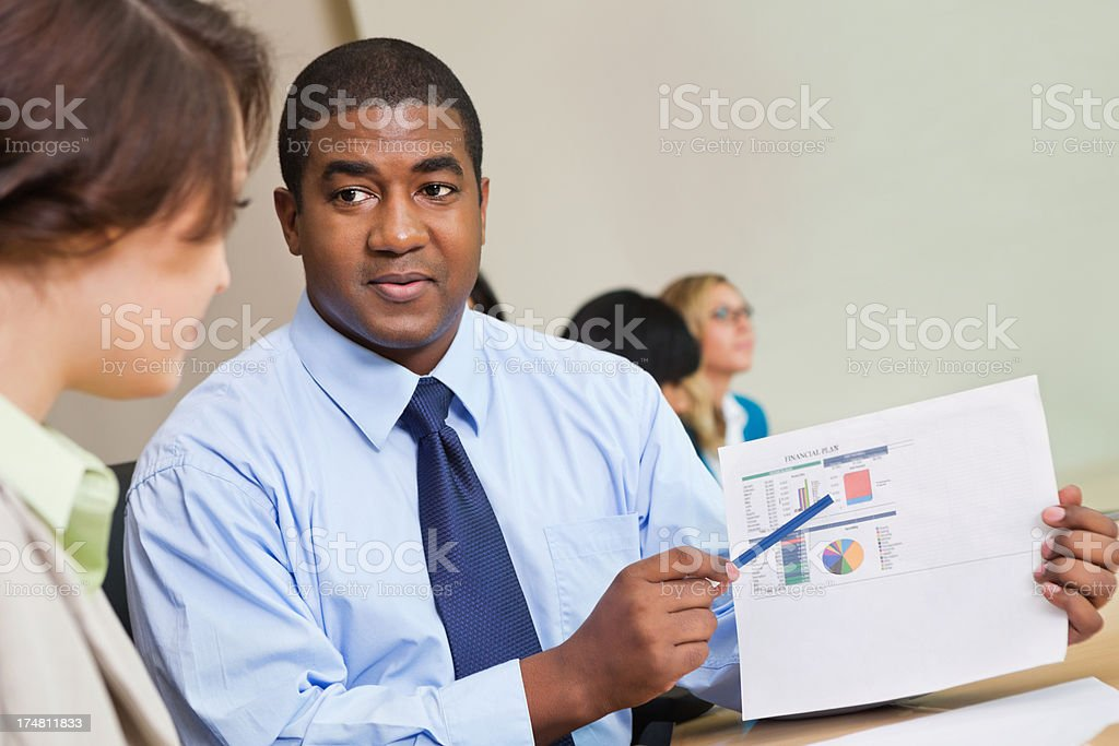 Financial advisor reviewing sales figures with client in meeting royalty-free stock photo