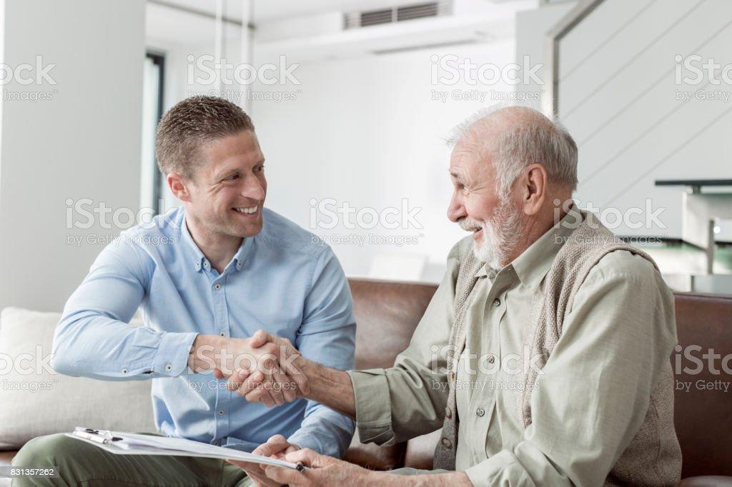 Financial advisor shaking hands with senior man stock photo