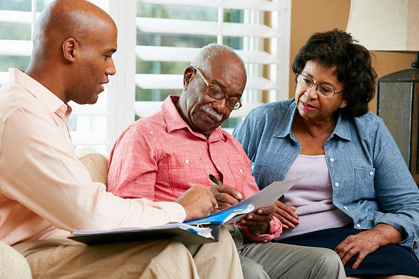 Financial Advisor Talking To Senior Couple At Home stock photo