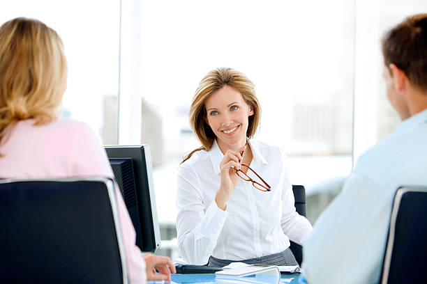 financial advisor with couple - bankers stock photos and pictures
